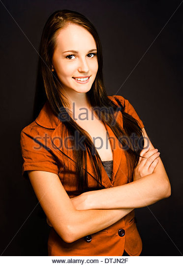 A smiling self-assured young female corporate executive exudes confidence and trust. - Stock Image
