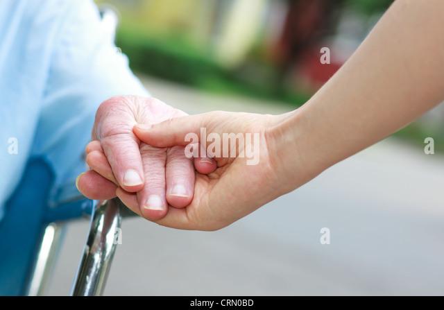 Senior women in wheelchair holding hands with caretaker - Stock Image