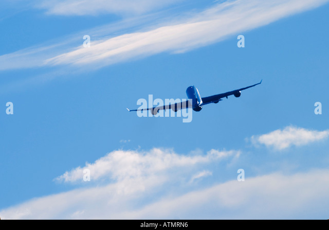Commercial airplane flying above white clouds and blue sky - Stock Image