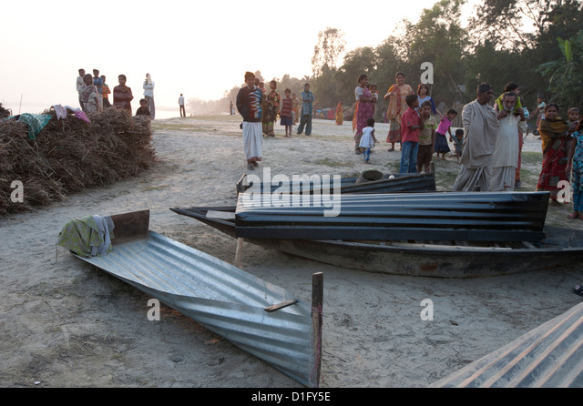 Villagers surrounding boats made from sheets of corrugated iron, lying on the banks of the River Hugli, West Bengal, - Stock Image