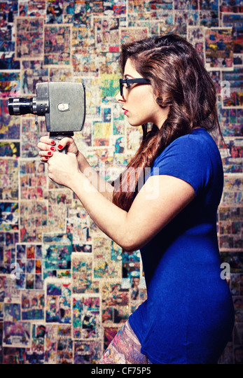 Woman holding a vintage cine camera. Textures added. Comic background - Stock Image