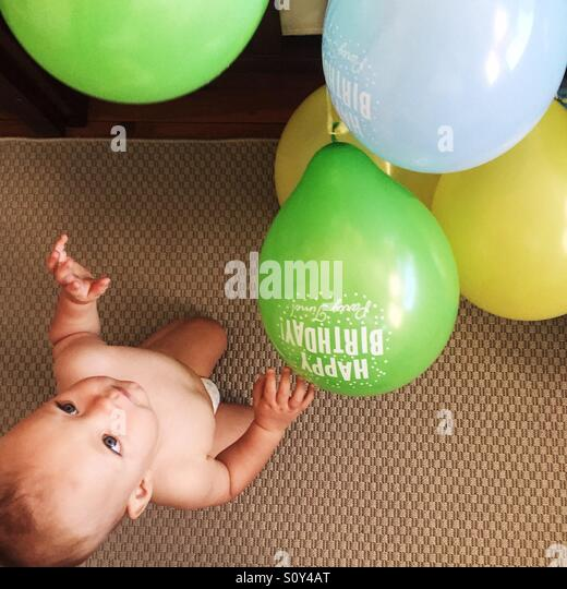 Birthday boy playing with birthday baloons - Stock Image
