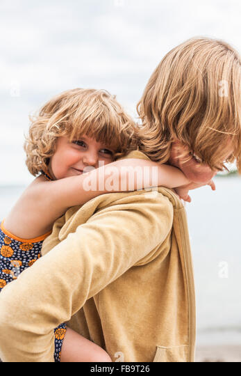 Sweden, Sodermanland, Stockholm Archipelago, Musko, Daughter (4-5) embracing mother - Stock Image