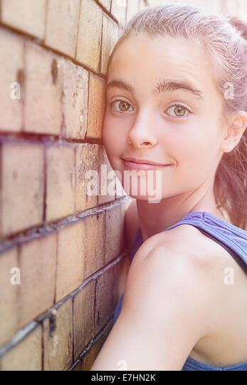 portrait of a smiling teenager girl leaning against a brick wall. - Stock Image