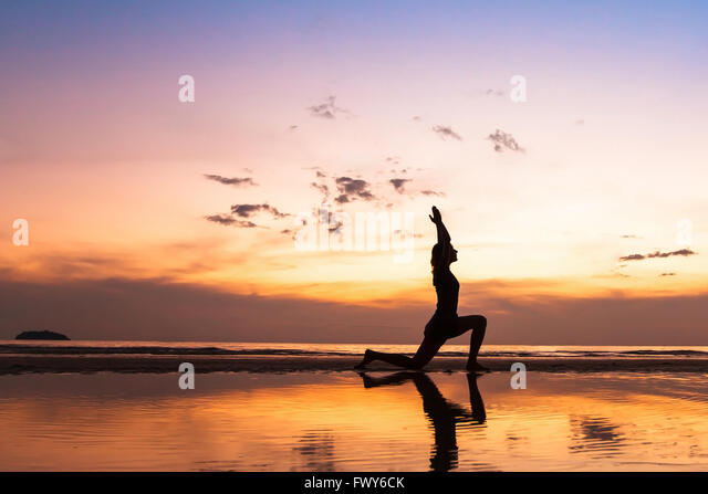 beautiful yoga exercise on the beach at sunset, background with copyspace - Stock Image