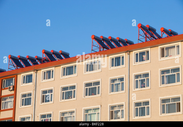 New Chinese apartments with solar water heaters on the roof. - Stock Image