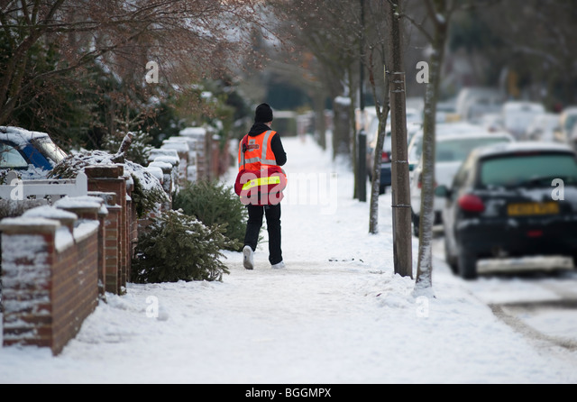 Postman delivering mail in winter weather - Stock Image