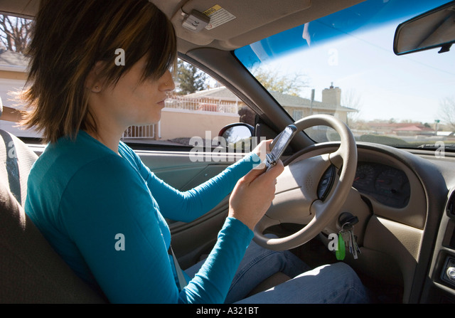 Young woman sitting in driver s seat of a car and looking at mobile phone - Stock-Bilder