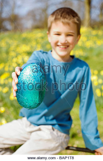 A young boy holding an Easter egg, smiling - Stock Image