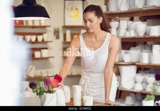 Female worker arranging craft products in workshop - Stock Image