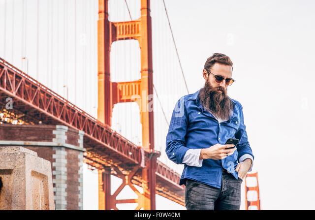 Man with beard checking smartphone at Golden Gate Bridge, San Francisco, California, USA - Stock-Bilder
