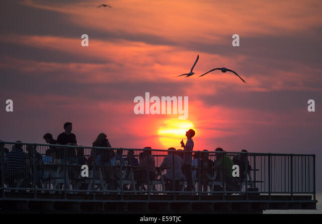 Aberystwyth, Wales, UK. 24th July, 2014. People relaxing on the pier at sunset, twilight over Cardigan Bay Aberystwyth - Stock Image