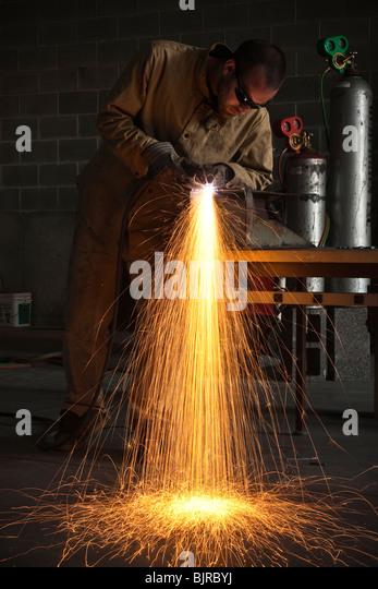 USA, Utah, Orem, man welding metal in workshop - Stock Image