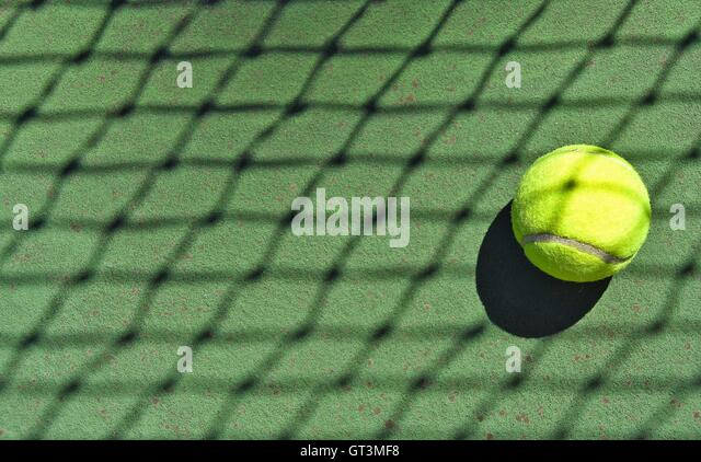 Crisscross net shadow on neon tennis ball. - Stock Image