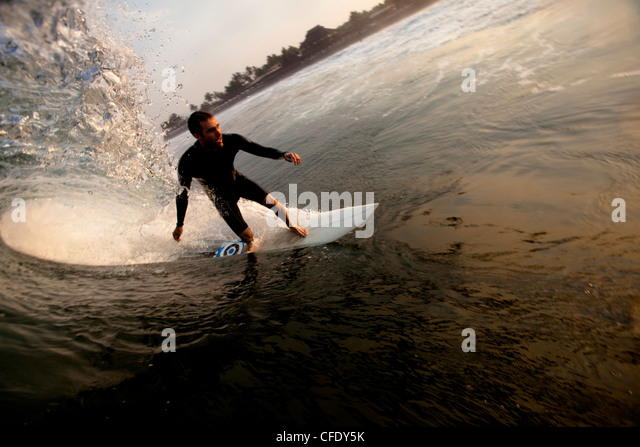 A male surfer sets up for a barrel while surfing the notorious beach break of Pasquales, Mexico. - Stock Image