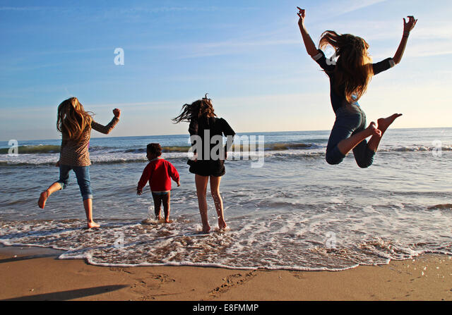 Four girls messing about on the beach, Barcelona, Spain - Stock Image