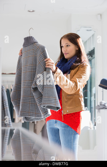 Young woman selecting sweater in store - Stock Image