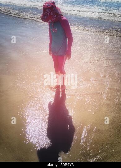 Talking to her shadow - girl standing at on the beach at the edge of the sea - Stock-Bilder