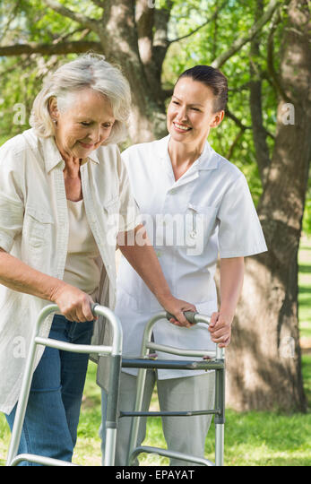 Female assisting mature woman with walker at park - Stock Image