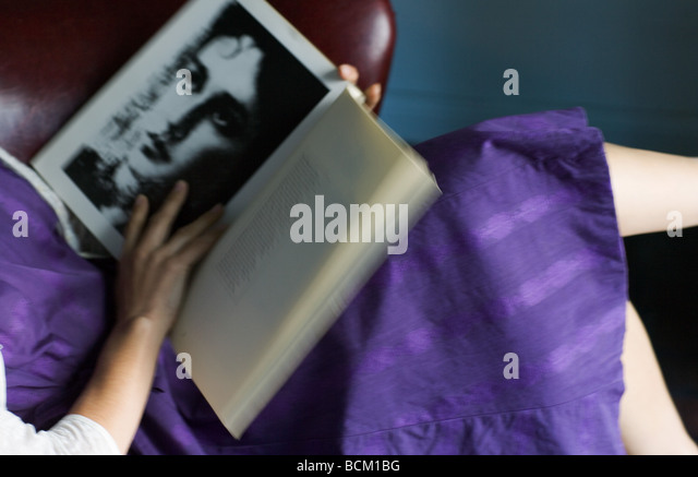 Woman in dress reading book of poetry, cropped view of mid section, high angle view - Stock-Bilder