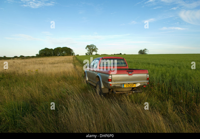 A pick up truck in a rural field - Stock Image