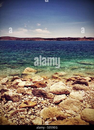Rocky shore leading to blue sea - Stock Image