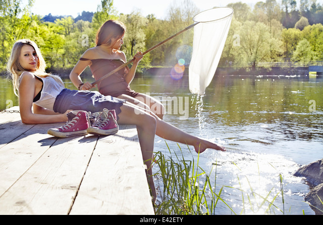Young women sitting on jetty, one holding fishing net - Stock Image