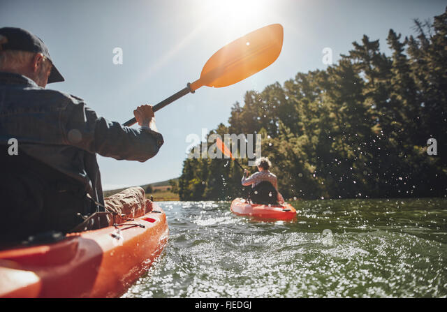 Outdoor shot of senior man canoeing in the lake with woman in background on a summer day. Man and woman in two different - Stock Image