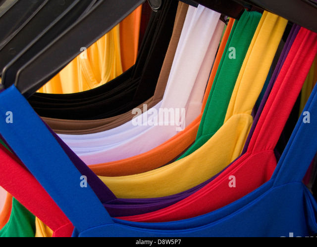 A row of colourful summer dresses hanging on plastic coathangers on a market stall, Arles, France - Stock Image