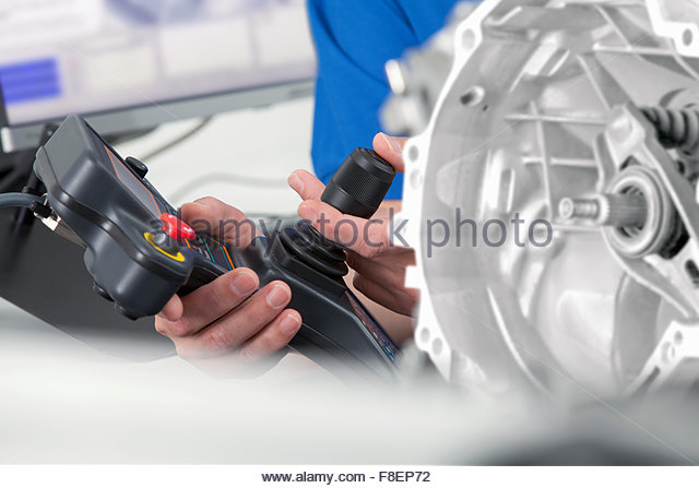 Close up of engineer with joystick controlling probe scanning engine block - Stock Image