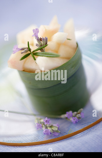 White peach salad with rosemary served in a banana leaf - Stock Image