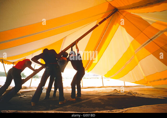 FOUR WORKERS STRUGGLE TO ERECT A LARGE YELLOW RENTAL TENT - Stock Image