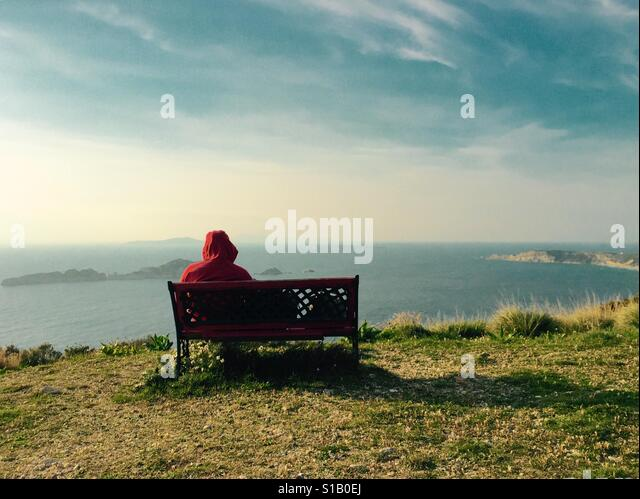 Man alone looking out over the sea from a bench. - Stock Image
