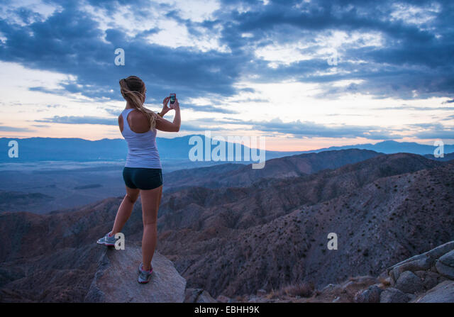 Woman taking photo of mountain, Joshua Tree National Park, California, US - Stock-Bilder