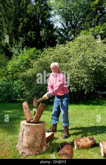 Senior man chopping logs in garden - Stock Image