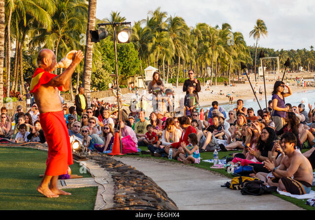 Hawaii Hawaiian Honolulu Waikiki Beach Kuhio Beach Park Hyatt Regency Hula Show performers free event man blowing - Stock Image