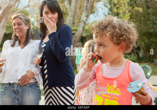 Young girl eating her cup cake at a party. - Stock Image