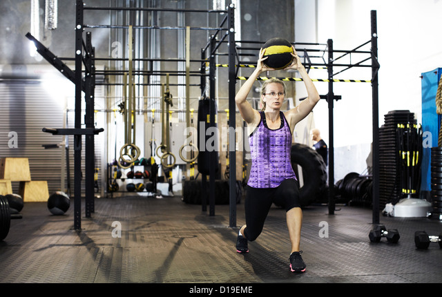Woman lunging and holding medicine ball above her head - Stock Image