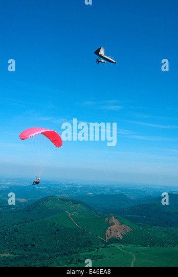 Paraglider and hang glider in the Auvergne Volcanoes Regional Park, France - Stock Image