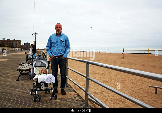 Man with baby boy in push chair at seaside - Stock Image