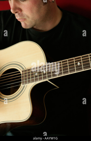 Tight portrait of man and guitar. - Stock Image
