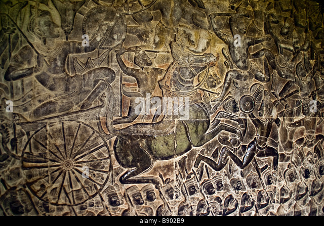 Angkor Wat bas relief stone carving of Mahabharata episode in west gallery depicting charioteer in battle pursuing - Stock Image