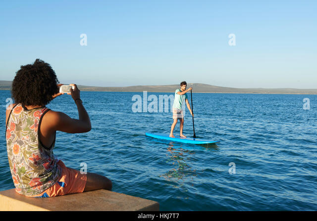 Young man photographing friend paddleboarding on sunny summer ocean - Stock-Bilder