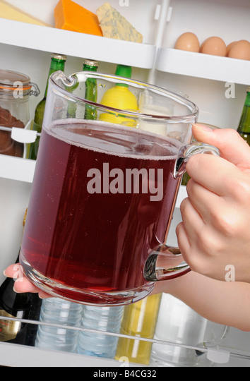 PUTTING JUG OF POMEGRANATE JUICE IN FRIDGE - Stock Image