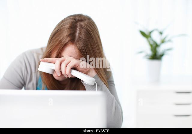 Depressed girl sitting behind laptop - Stock Image