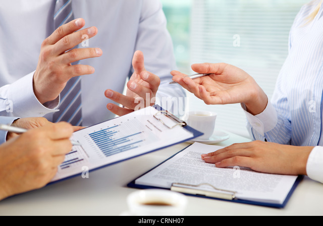 Business group discussing the present state of business affairs - Stock Image