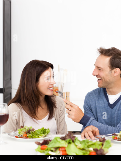 Man giving a tomato to his girlfriend during lunch - Stock-Bilder