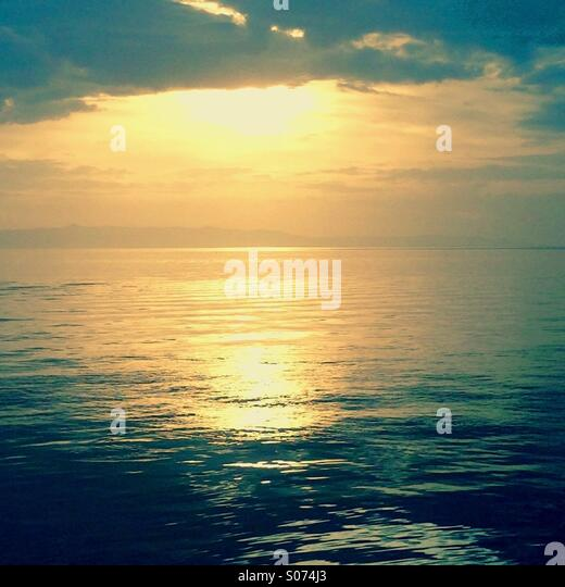 Sunset at sea with sun reflection - Stock Image