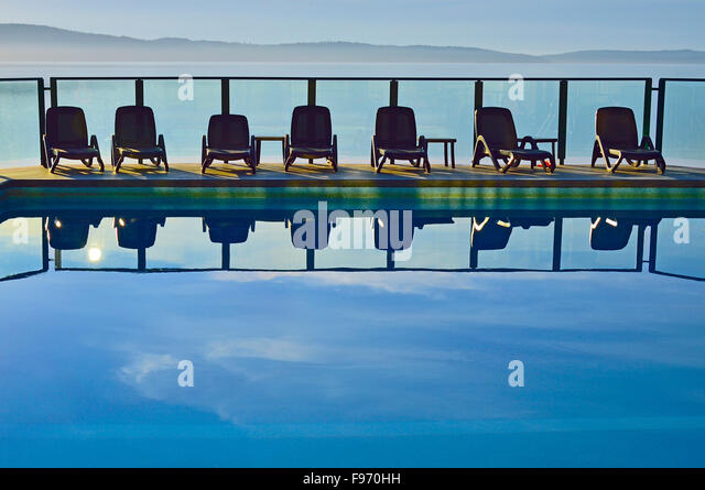 A horizontal image of  a line of chairs at an outdoor swimming pool at vacation resort on Vancouver Island B.C. - Stock Image