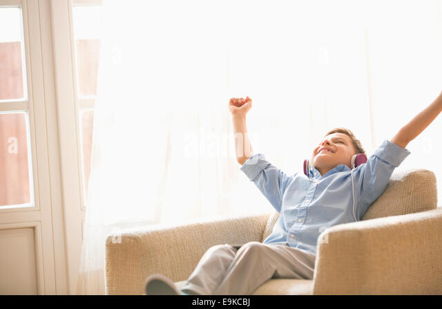 Happy boy with arms raised enjoying music while relaxing on armchair at home - Stock Image
